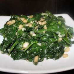 Spinach and Pine Nuts Recipe -  Pine nuts seem to add a bit of glamour to just about anything. Here it 's spinach. Garlic, cooked spinach and the pine nuts are cooked in olive oil for a minute or two and seasoned with freshly ground pepper.