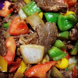 Chinese Pepper Steak Recipe and Video - Beef top sirloin steak is sliced across the grain for tenderness, coated in a sweet-and-savory soy sauce marinade, then quickly stir fried with fresh green pepper, onion, and tomatoes.