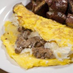 Candice's Lasagna Omelet Recipe - Now you can enjoy lasagna for breakfast with this hearty and simple lasagna omelet, stuffed with cheese, sausage, and tomato sauce.