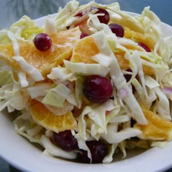 Cranberry Coleslaw Recipe - Sweet-tart and crunchy, this unusual slaw is enlivened by a combination of cabbage, sugared cranberries and thin orange slices.