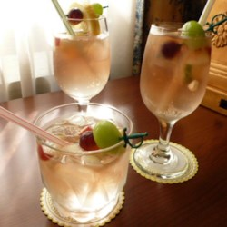 Rachel's Rose Sangria Recipe - Dress up traditional sangria by adding green and red grapes, plus diced apple, lemon and lime to a sparkling pink mix of rum, brandy, white Zinfandel wine, and lemon-lime flavored soda.