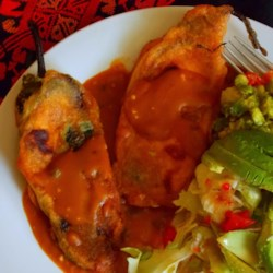 Chiles Rellenos Autenticos Recipe - Authentic Mexican stuffed peppers start as fresh poblano peppers, roasted in the oven, skinned, and stuffed with cotija cheese. Floured and dipped in egg, the peppers are fried to tasty golden brown.