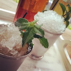 Mint Juleps Recipe - Sit on the front porch in your rocking chair on a sultry afternoon and sip on one or two of these.  The proper way to serve a mint julep is in a frozen silver goblet, but you can use glasses instead--just use the most elegant ones you have!  You can make the syrup ahead of time and store it in the refrigerator for whenever the julep mood strikes you.