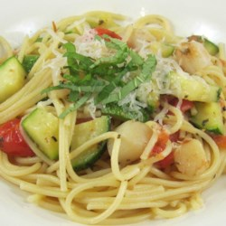 Pasta with Scallops, Zucchini, and Tomatoes Recipe - Bay scallops, chopped tomatoes and fresh basil are added to a saute of garlic and zucchini, then poured over fettuccini for an elegant seafood dish. Serve as an entree or appetizer.