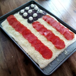Flag Pizza Recipe - Show your USA pride with this patriotic pizza! With pepperoni for the stripes, purple potatoes for the sky, and mozzarella balls for the stars, you'll find yourself saluting with every slice!