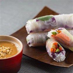 Spring Rolls with Coconut Peanut Sauce Recipe - Strips of carrot, bell pepper, cucumber and shredded red cabbage and more are rolled into rice noodle wrappers and served with a creamy peanut sauce.