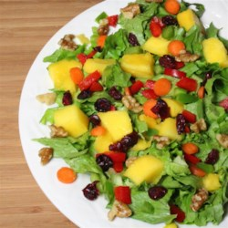 Mango Walnut Salad Recipe - Succulent mangoes star in this easy summer salad that's made in minutes simply by peeling and cutting up the fruit, then tossing it with walnuts, cranberries, lettuce, and sliced red and green bell peppers.