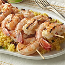 Shrimp with Fruited Couscous Recipe - This easy shrimp changes expectations on recipes worthy of backyard barbecues. An herb-yogurt-balsamic marinade brings a pop of tangy flavor to the skewered seafood. Serve on a bed of so-simple couscous dotted with orange peel and dried cherries.