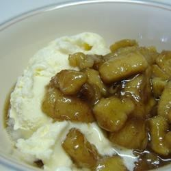 Slow Cooker Bananas Foster Recipe - Banana slices are cooked in a rich butter and rum sauce with walnuts and coconut. Serve warm over vanilla ice cream.