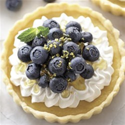 Lemon Blueberry Tartlets Recipe - These pretty little tarts with a creamy lemon filling are topped with whipped cream and fresh blueberries.