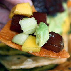 Ahi and Avocado Poke Tower Recipe - Cubed fresh avocado, cucumber, and mango are layered into a tower and topped with marinated ahi tuna for a delicious appetizer or salad.