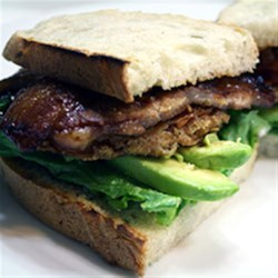Grilled Pork Belly BLT with Fried Tomatoes and Avocado Recipe - Grilled pork belly, pan-fried tomato slices, fresh avocado and crisp leaf lettuce on artisan bread bring a gourmet twist to a classic sandwich.