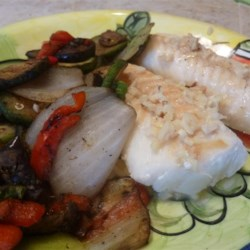 Cod with Lemon, Garlic, and Chives Recipe - Simple baked foil pouches contain a fillet of cod, fresh lemon slices, garlic, and chopped chives for a flavor combination that enhances the taste of the fresh fish.