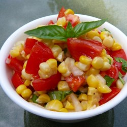 Summer Corn Salad Recipe - This fresh and flavorful salad features buttery yellow corn tossed with chunks of tomato and onion with a fresh basil vinaigrette.