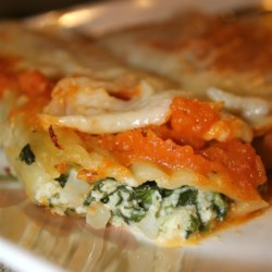 Jo's Manicotti Recipe - Hearty tubes of manicotti are stuffed with a rich blend of ricotta and Romano cheeses, spinach, eggs, onion, garlic and thyme, drizzled with a simple tomato sauce, sprinkled with mozzarella and baked until bubbly.