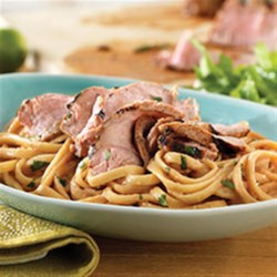 Thai Pork Noodle Bowl Recipe - Be internationally inspired! Slice tender grilled Thai-marinated pork chops and top a bed of peanut noodles made with garlic, lime juice and soy sauce.