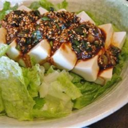 Spicy Tofu Salad Bowl Recipe - This spicy tofu salad bowl recipe includes layering rice, romaine lettuce, cucumbers, and tofu in a bowl and topping it with a spicy sauce for a quick Asian-inspired meal.