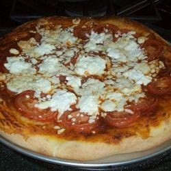 Goat Cheese and Tomato Pizza Recipe - This homemade pizza substitutes goat cheese for mozzarella. You can use the sauce recipe, or use store-bought sauce to make it easier. You can always add any other ingredients - artichoke hearts make a great addition!