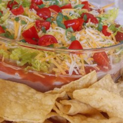Taco Salad Dip Recipe - This fusion of a Mexican-style layered dip with a salad would be perfect for your Cinco de Mayo luncheon.