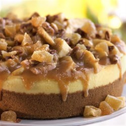 Apple Butter Cardamom Cheesecake Recipe - Traditional cheesecake is topped with apple slices cooked with apple butter, cardamom and pecans and garnished with whipped cream and crystallized ginger pieces.