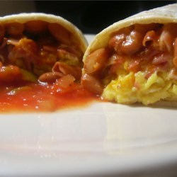 Breakfast Burritos Recipe - A different way to start your day.  Burritos with fried eggs, bacon and refried beans topped with melted cheese.  Ham or sausage may be substituted for the bacon.  Serve with salsa on the side.