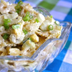 Dad's Potato Salad Recipe - A big bowl of tangy potato salad has spiral pasta, hard-boiled eggs, green onions, and dill pickles, all in a creamy mayonnaise dressing.