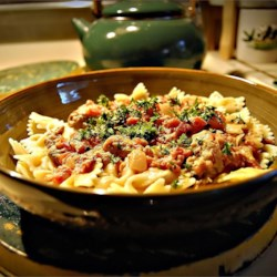 Bow Ties with Sausage, Tomatoes and Cream Recipe - Sweet Italian sausage is simmered with plum tomatoes, garlic, onion and heavy cream to create a thick, rich sauce that's served with bow tie pasta.