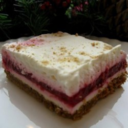 Layered Raspberry Dream Recipe - A lovely layered raspberry dessert has a graham cracker crust, a layer of cream cheese filling, and raspberries in gelatin, all topped with whipped topping and a sprinkle of graham cracker crumbs.