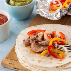 Easy Flank Steak Fajitas Recipe - Marinated steak strips and flavorful veggies make a delicious fajita filling--perfect for busy weeknight dinners.