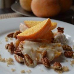 Peaches and Cream Recipe - A fresh peach is sprinkled with brown sugar, dolloped with sour cream and topped with pecans.