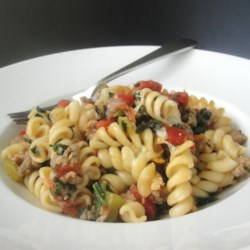 Tomato, Spinach, and Cheese Pasta Recipe - This easy weeknight meal has baby spinach hidden in melted cheese and tomatoes. Your kids will love it!