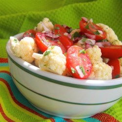 Crunchy Cauliflower and Tomato Salad Recipe - Cauliflower and cherry tomatoes make a festive duo in this crunchy salad with a light dressing. Bring to any summer picnic or Memorial Day barbeque.