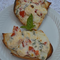 Baked Cheese Spread Recipe - Cream cheese, fresh mozzarella, fresh basil, and tomatoes are melted, spread on sourdough bread, and broiled into a crowd-pleasing, cheesy appetizer.