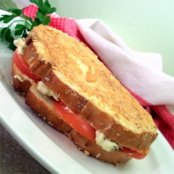 Gourmet Grilled Cheese Recipe - Tangy goat cheese, tomatoes, and a crispy coating of grated Romano cheese set these sandwiches above the rest.