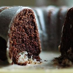 Chocolate Macaroon Tunnel Cake Recipe - This cake recipe is the result of a discontinued, but wonderful box mix. It is a chocolate cake that slices to reveal a beautiful white coconut center. Yummy! The vanilla glaze can easily be made into chocolate by adding 2 tablespoons of cocoa powder.
