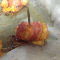 Bacon-Wrapped Tater Tots(R) Recipe - Potato nuggets are stuffed with Cheddar cheese and wrapped in bacon for a crowd-pleasing party food.
