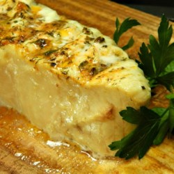 Cedar Planked Halibut Recipe - Halibut steaks are 'planked,' barbequed on a water-soaked cedar plank, and basted with a succulent herb and butter sauce.