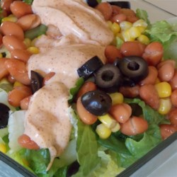 Mexican Salad Bowl Recipe - A creamy, spicy dressing is served with a bowl of lettuce, corn, olives, and kidney beans in this Mexican-influenced salad idea.