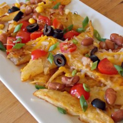 Quick Potato Nachos Recipe - Crisp, golden brown potato slices are covered with cheese, beans, tomatoes, olives, green onions, and green chiles in this potato nacho recipe that is perfect for game day.