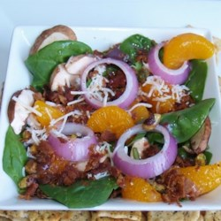 Spinach and Mandarin Orange Salad Recipe - A spinach and mandarin orange salad with bacon and slivered almonds gets a new twist with a warm homemade dressing that is sure to impress your guests.