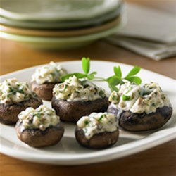 Chicken-Stuffed Mushrooms Recipe - Mushroom caps filled with a creamy onion, garlic, and diced chicken mixture are baked until piping hot for a crowd-pleasing party appetizer.