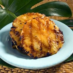 Honeysuckle Pineapple Recipe - Chunky wedges of fresh pineapple are marinated in honey, cherry brandy and lemon juice, and then they're grilled until they're hot, caramelized, and irresistible.