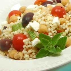 Greek Couscous Recipe - Large pearls of Israeli couscous combine with garbanzo beans, feta cheese, sun-dried tomatoes, and Greek olives to make a side dish or light main dish that's perfect for a hot summer's day.