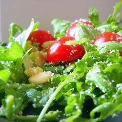 Easy Arugula Salad Recipe - This salad is shaken, not tossed. All the ingredients - arugula, cherry tomatoes, pine nuts, Parmesan cheese and an oil and vinegar dressing - are combined in a plastic bowl with a lid and given a few shakes. Topped with avocado slices, it is very presentable for guests.