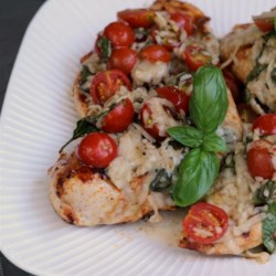 Caprese Chicken Recipe - Chicken breasts are marinated in Italian dressing, seared in a hot skillet, and baked with mozzarella cheese and tomato slices. The chicken is topped with fresh basil leaves and a drizzle of balsamic vinegar. Start marinating in the morning and finish cooking when you get home.
