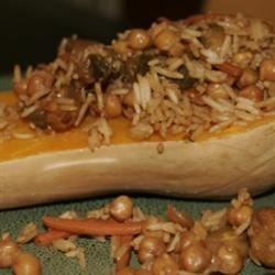 Stuffed Butternut Squash Recipe - Brussels sprouts, carrots, and garbanzo beans simmered with soy milk, tamari, and garlic, are tossed with basmati rice and spooned into baked butternut squash. A delicious vegetarian and vegan main dish.