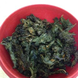 Cheesy Kale Chips Recipe and Video - Crispy, oven-baked kale chips seasoned with nutritional yeast for a cheese-like flavor.