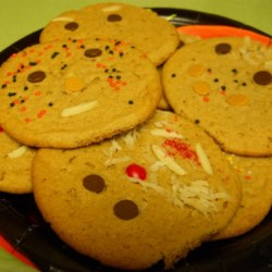 Halloween Cookies Recipe - Make Halloween faces using peanuts, raisins, chocolate or butterscotch chips or red candies for eyes, nose and mouth.  Use colored coconut or chocolate sprinkles for hair.