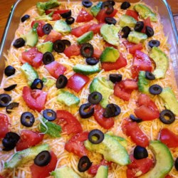 Sandie's Seven-Layer Bean Dip Recipe - Refried beans, ground beef, sour cream, tomatoes, and Mexican cheese-blend are baked into a crowd-pleasing 7-layer dip; serve with tortilla chips.