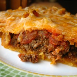 Taco Pie Recipe and Video - A pre-baked crust of refrigerated crescent-roll dough is filled with a mixture of browned ground beef and taco seasoning layered with sour cream, shredded cheese, and crushed nacho chips. It is returned to the oven for about 10 minutes.